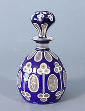 FLACON ovoïde et son bouchon en verre triplé d'émail bleu de Sèvres sur émail blanc, taillé de motifs en trèfles et de réserves ovales à décor de rinceaux dorés..Haut.