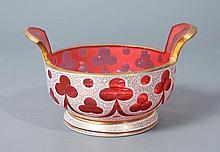 VIDE-POCHE en forme de baquet à anses en verre rose doublé d'émail blanc à résille dorée, taillé à motifs de trèfles stylisés. Haut