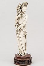CHINE (XX°). SUJET en ivoire sculpté représentant une élégante tenant un bouquet. Socle en bois vernis. H 22,5cm