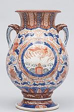 JAPON (XIX°). VASE à anses en porcelaine Imari à décor en bleu sous couverte et rouge de fer à motif de phoenix dans des cartouches. H 32cm