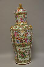 CHINE (XIX°). VASE couvert en porcelaine de Canton à décor de la famille Rose. Le frétel du couvercle à décor d'un chien bouddhique.  H 66,5 cm (accidents et fêles)