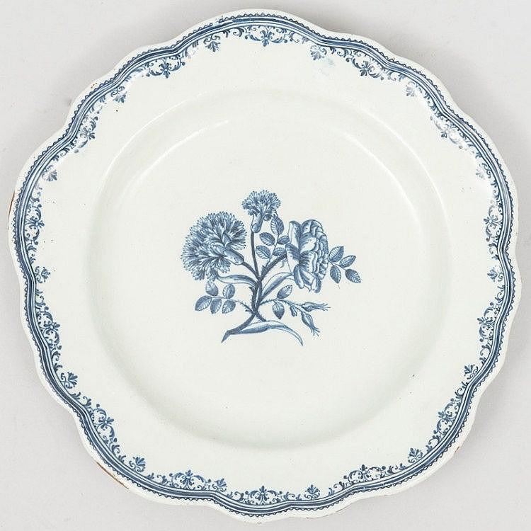 MOUSTIER (faïence de) fabrique de Clérissy Grand PLAT creux, forme orfèvrerie, décor de bouquet groupé au bassin et frise d'arabesques façon dentelle autour de l'aile, à filets émail stannifère légèrement bleuté. Vers 1745-1750 diam. 37 cm, éclats et