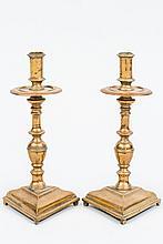 Paire de chandeliers en bronze reposant sur une base triangulaire moulurée ; fût tourné en balustre