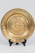 Plat d'offrandes en laiton. Centre orné d'une couronne de godrons en spirale entouré d'un rinceau feuillagé entrelacé ; aile à motifs poinçonnés.