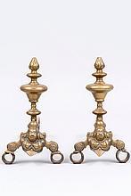 Paire de chenets dits au marmouset en bronze ; fûts tournés en vase et sphère aplatie avec bouton terminal en forme de flamme ; fer à volutes.