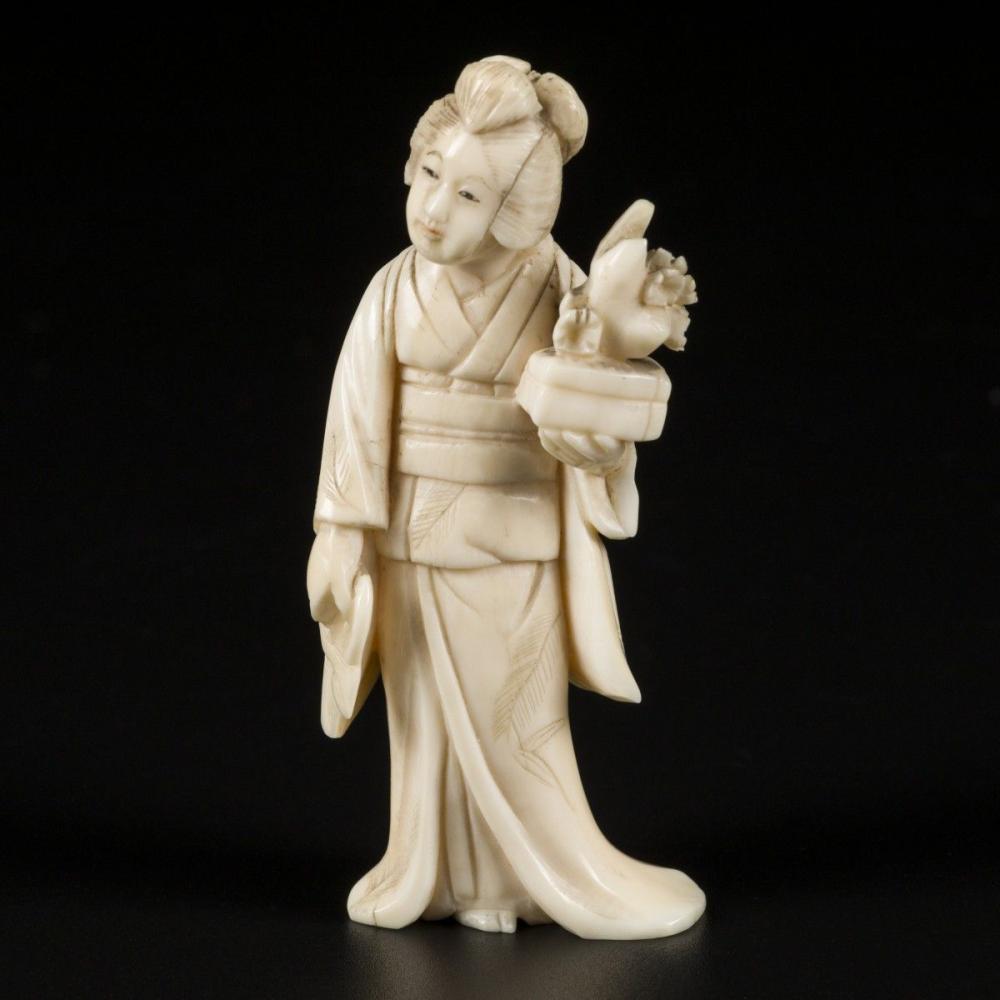 An ivory okimono of a Japanese lady wih a bonsai tree. Japan, late Meiji period.