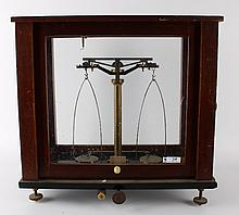 An apothecary scales in walnut cupboard, early 20th century.