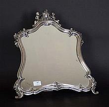 Fin miroir à poser en métal argenté à décor aux amours portant le cartouche - Hauteur : 48 cm