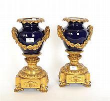 Paire de vases du XIXème siècle en porcelaine à fond bleu Sèvres et montures en bronze doré de mufles de bouc et guirlandes florales Louis XVI - Hauteur : 37 cm