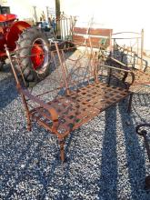 Pair of decorative metal garden benches with cushions.
