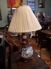 Oriental ceramic table lamp with cloth shade.