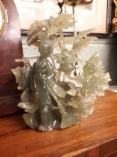 Oriental jade carving mounted on wooden stand.
