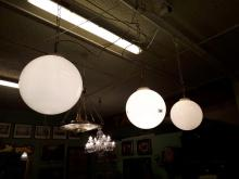 Set of three opaline glass football hanging light shades.