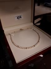 Single strand pearl necklace with gold links.