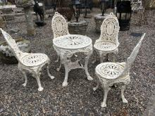 Set of four cast iron garden chairs and a circular table.