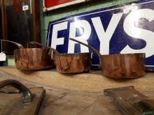 Three 19th. C. graduated copper saucepans.