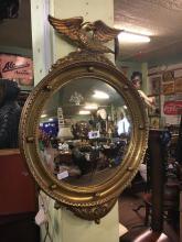 Edwardian gilt convex mirror surmounted with an eagle.