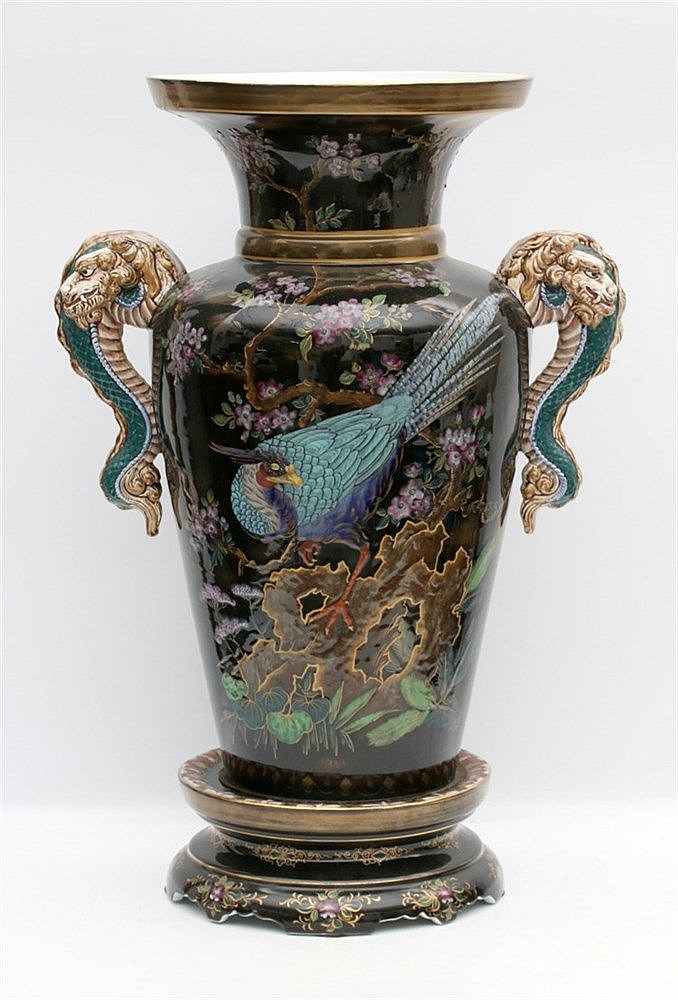 A large ceramic vase on a separate base, decorated with two col