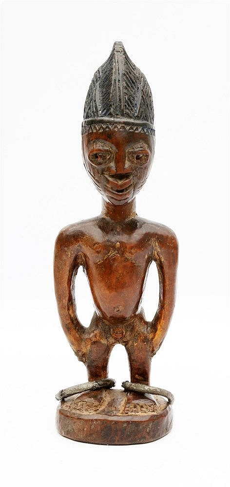 A wooden Ibeji twin figure with lead anklets and blue pigmented
