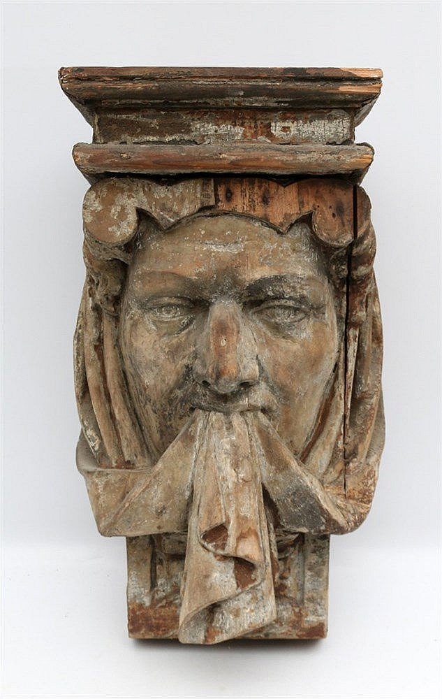 An oak corner brace with a sculpture of a male head with a cloth