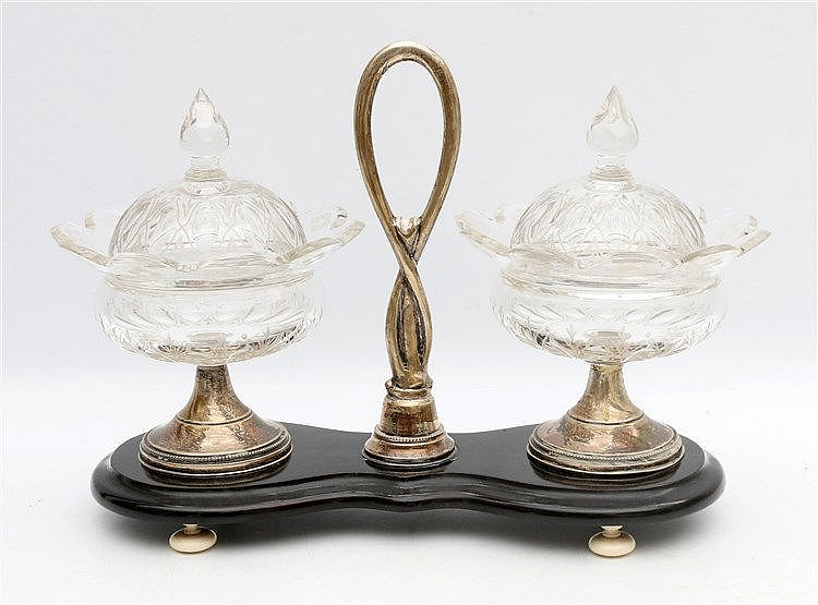 A rock sugar set with two cut cristal lids on a silver base. The