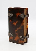 A tortoise shell book cover with silver mounts. Inside a book 'H