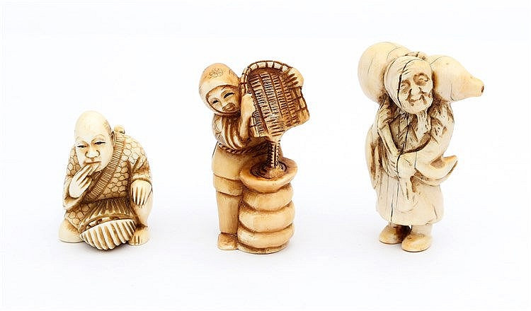 A group of three Japanese ivory netsuke, one carved as a man wit
