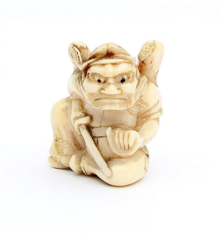 A Japanese ivory netsuke carved as an oni carrying a sword in