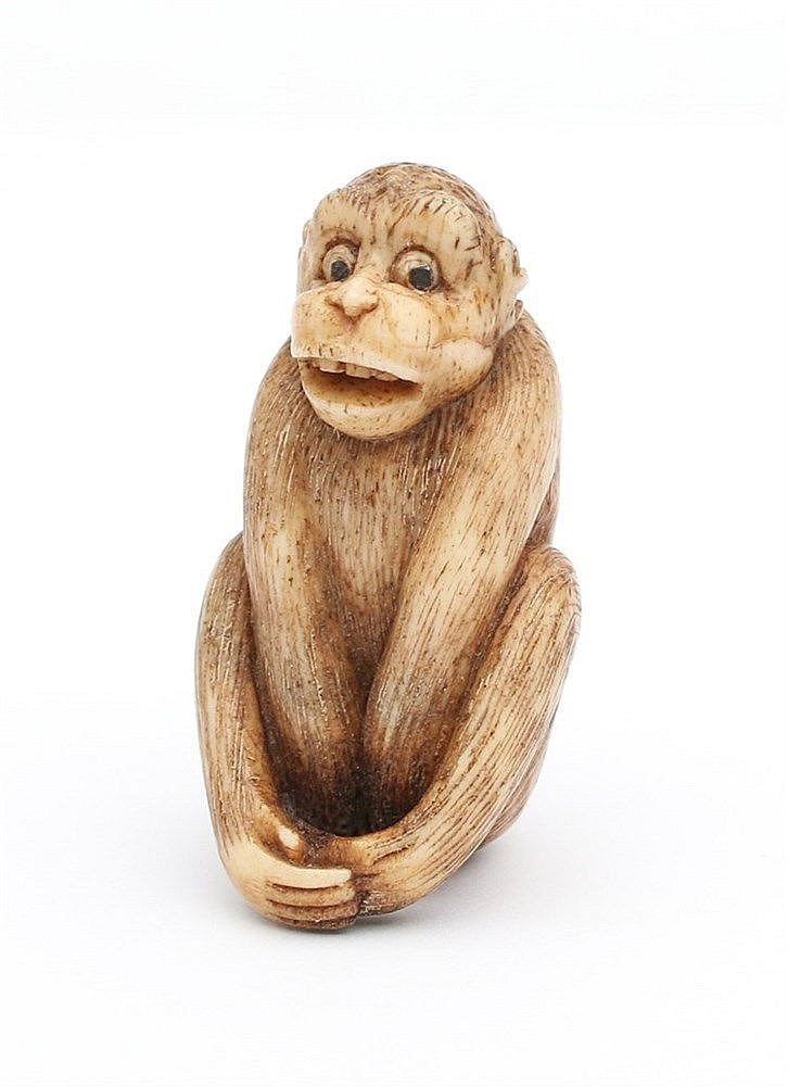 A Japanese bone netsuke carved as a seated monkey. Circa 1900.