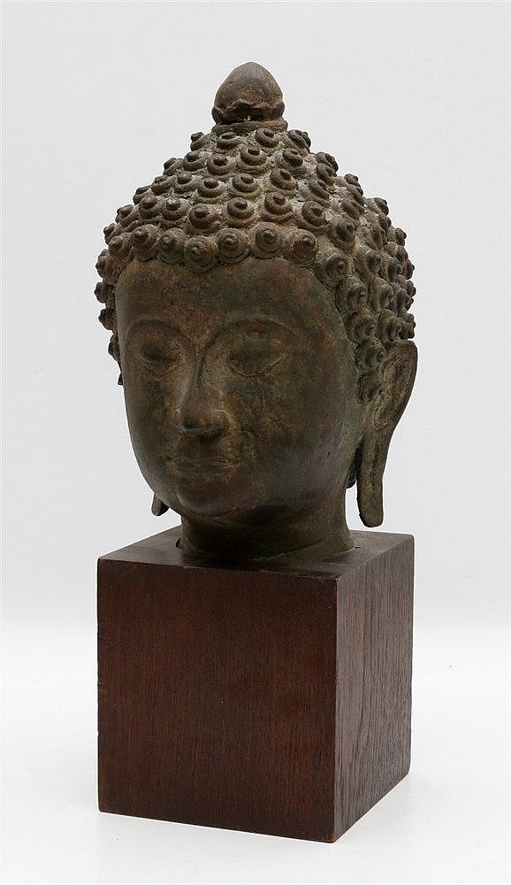 A bronze head of Buddha, his face with serene exporession, with