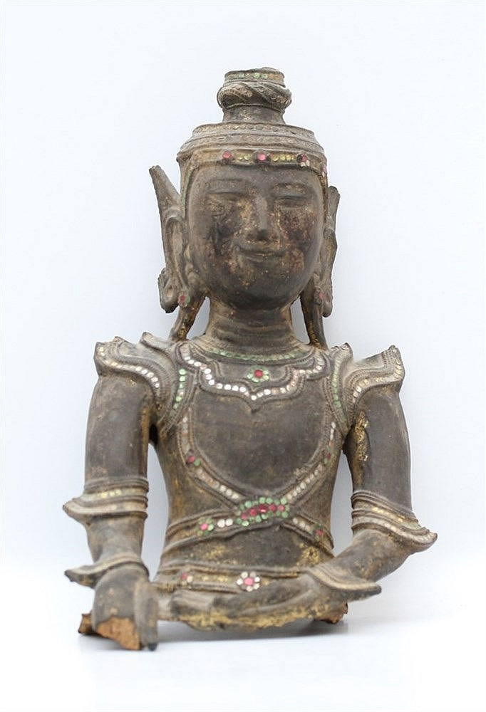 A Burmese wood bust of Buddha, his dress and jewellery inlaid wi