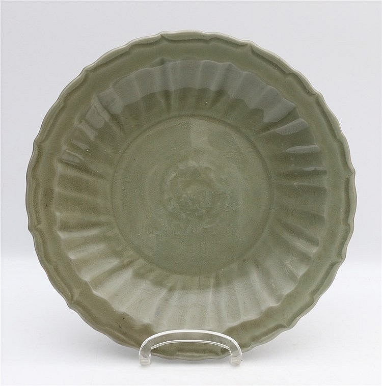 A Chinese celadon dish with fluted well and a floral relief meda