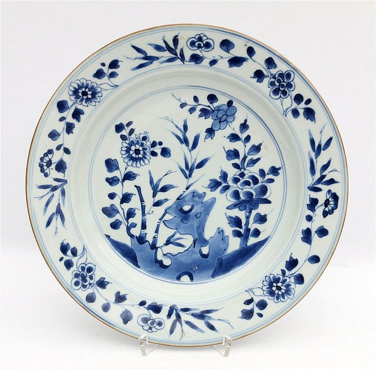 A Chinese blue and white plate decorated with flowers and bamboo