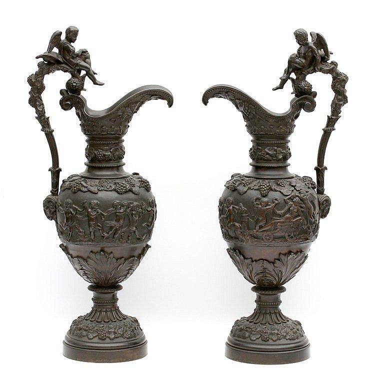 A pair of bronze ewers. Each with a cherub mounted handle, the b
