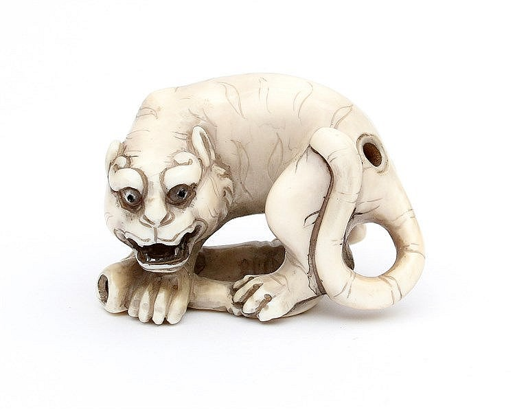 A Japanese ivory netsuke carved as a tiger on a stalk of bamboo.