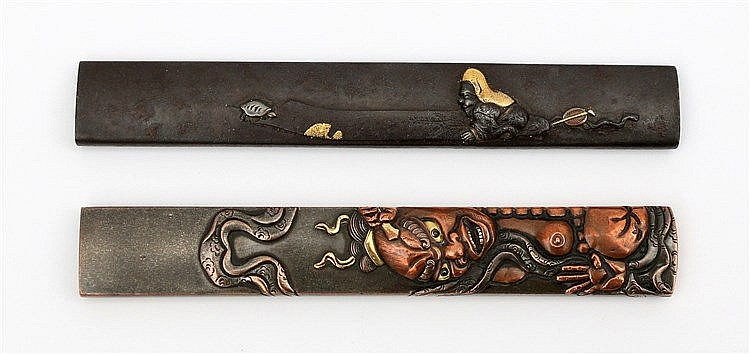 A Japanese iron kozuka with relief decoration of a man with a t