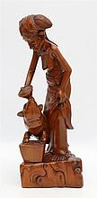 A wooden sculpture. An older woman feeding a pig. Signed on base