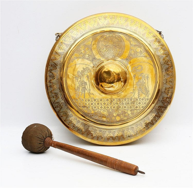An Indonesian brass gong incised with wajang figures and stylise