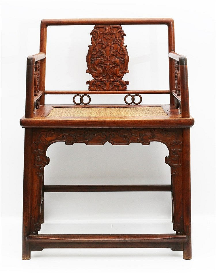 A Chinese wood armchair carved with archaistic dragons and cash