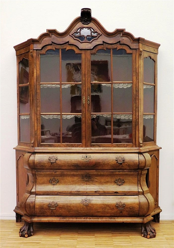 A walnut display cabinet with carved hood. The upper part with t