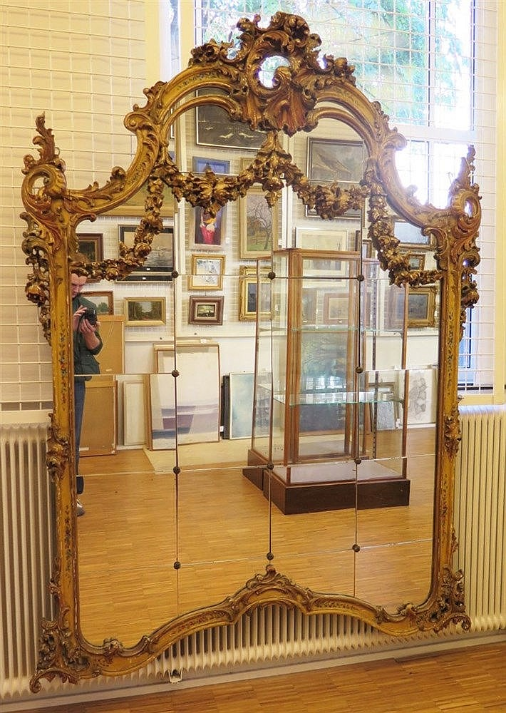 A giltwood mirror. The frame partly decorated with flowers. Fran