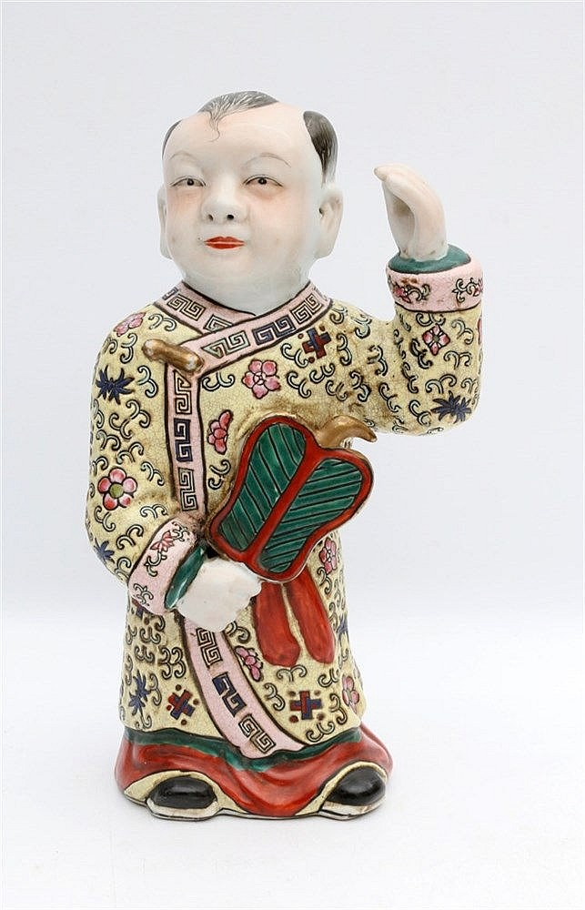 A Chinese famille rose figure of a boy. Hoogte 26,5 cm.