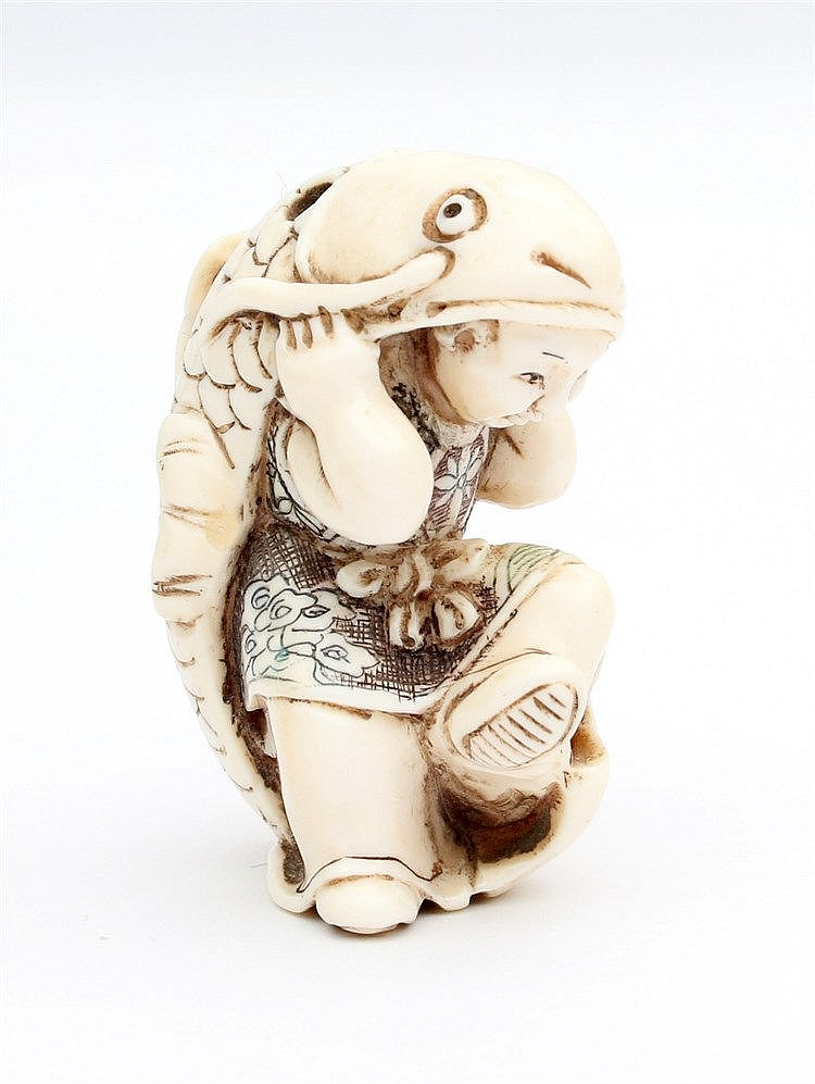 A Japanese ivory netsuke shaped as a boy in a carp costume. Meij