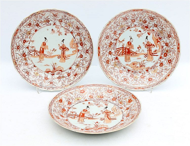 A set of three iron-red and gilt decorated plates, painted with