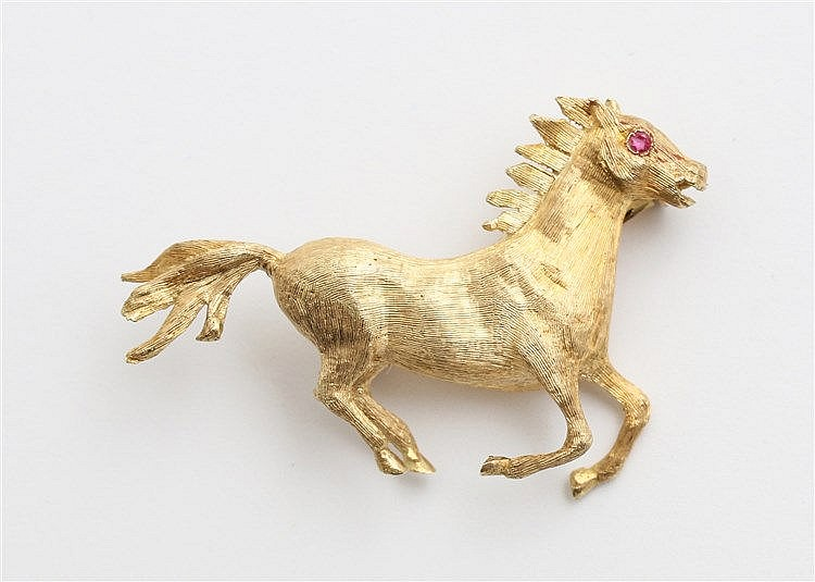 Yellow gold brooch, galopping horse. Ruby set eye.  Weight 8.1