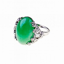 Ellis Bros. Platinum Ring, set with an oval jadeite cabochon (16.4mm x 11.3mm x 6.4mm) and decorated with 2 small bullet cut and 30 small single cut diamonds