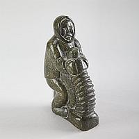 "TIMOTHY KUTCHAKA (1924-), E9-774, InukjuakHUNTER TWISTING A SKIN, stone, disc number inscribed, 9.75"" x 3"" x 6"" - 24.8 x 7.6 x 15.2 cm."