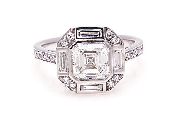 A DIAMOND RING of Art Deco style, centred with a square emerald-cut diamond
