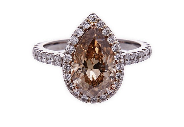 A DIAMOND RING centred with a pear-shaped Orange-Brown diamond weighing 3.0
