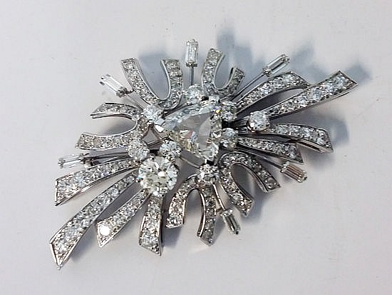 A DIAMOND BROOCH of stylised design, centered with round brilliant- and tri